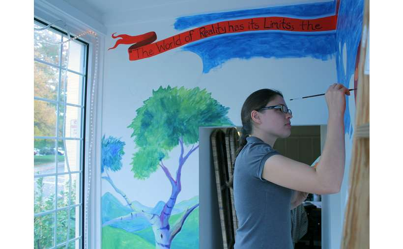 Artist Emily Thomson painting mural for LARAC's display case window