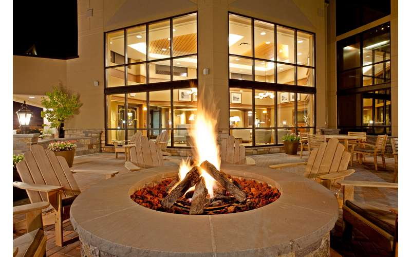 a fire pit surrounded by rustic chairs near a hotel