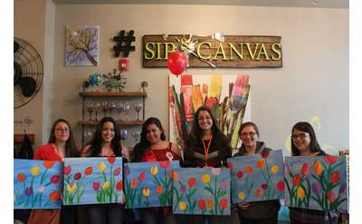 people holding paintings of flowers at sip and canvas
