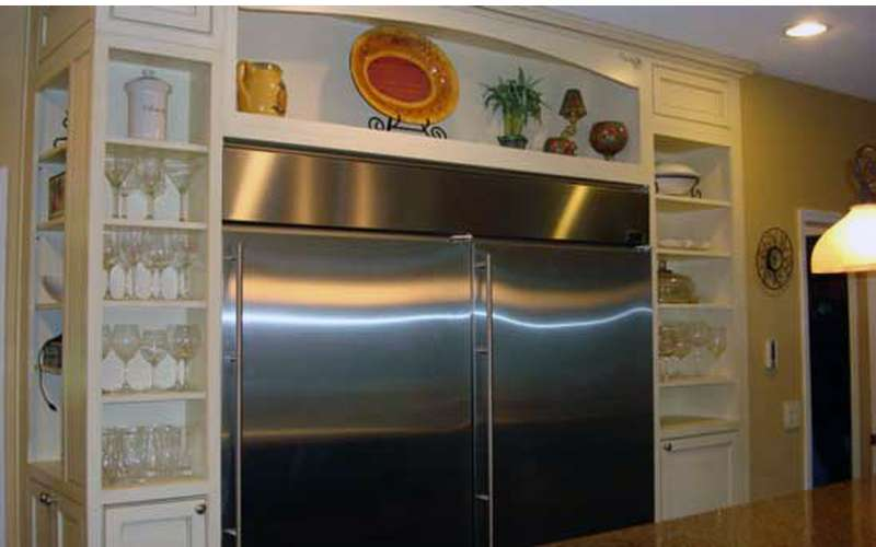 Adirondack Home Renovations had created a beautiful, custom built-in space for this commercial-sized refrigerator.