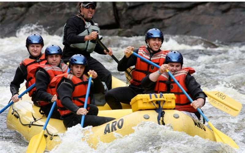 rafting group dressed in black long sleeved gear on the river