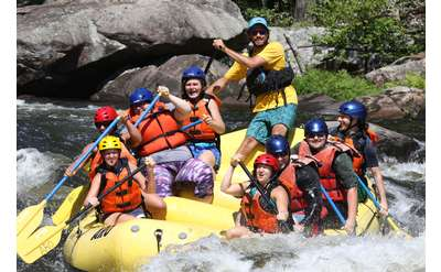 large group of whitewater rafters on a yellow raft