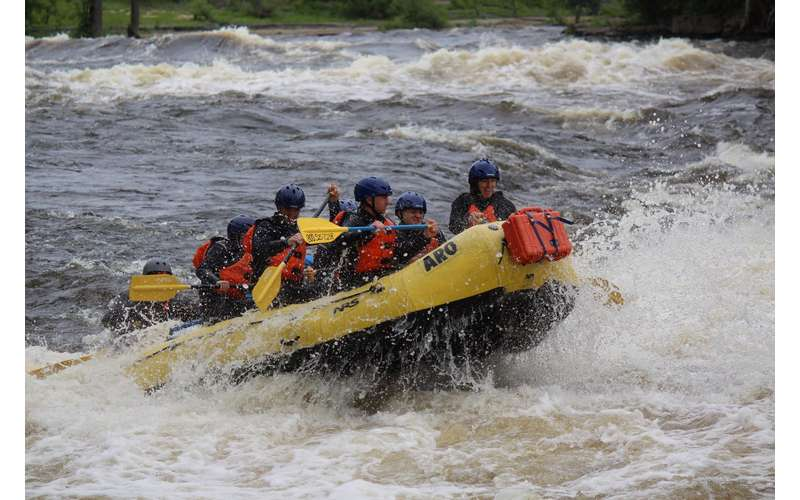 a group of whitewater rafters going over a small wave in the rapids