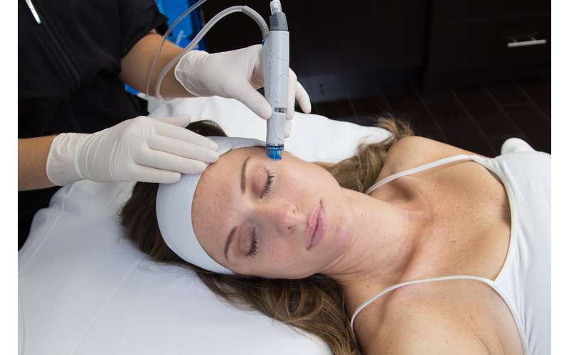 a woman receiving a hydrafacial treatment while on a bed