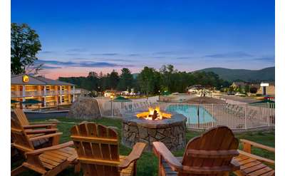 a fire pit with chairs and an outdoor pool at evening