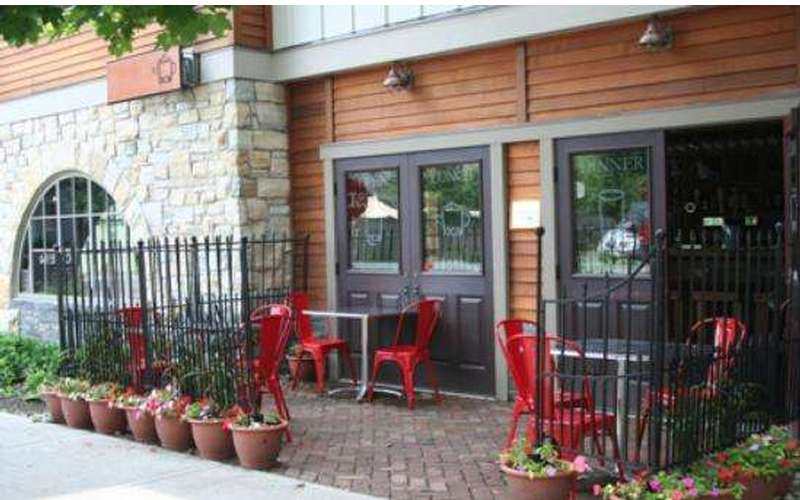 an outdoor patio with red chairs at a restaurant