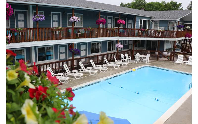 View of the heated pool and beautiful flowers at Lake Haven Motel