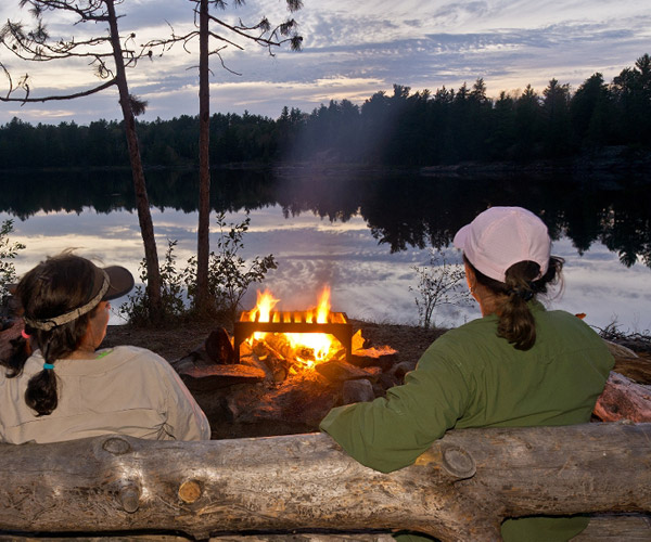Couple enjoying the campfire by the lake