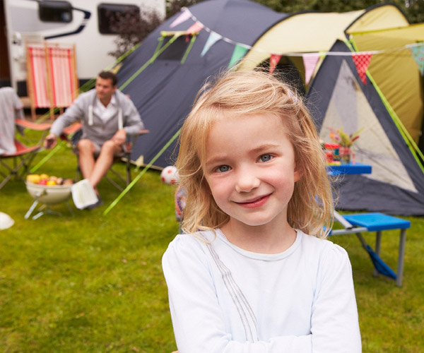 Young girl with tent and RV in background