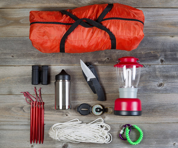 Several camping supplies on a picnic table