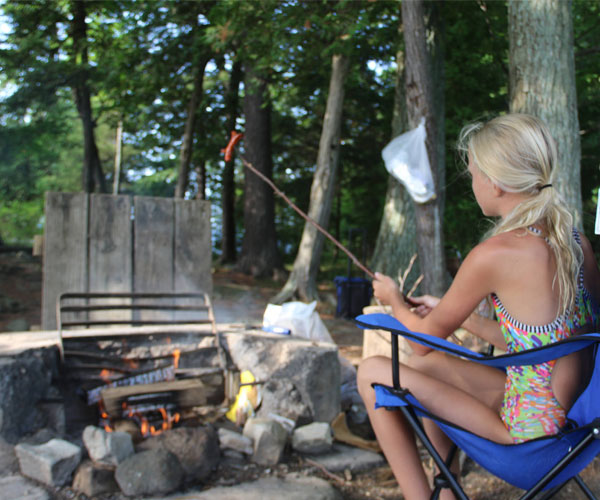Cooking franks over the fireplace on a Lake George island