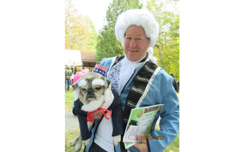 man dressed in colonial costume holding pug dressed in costume