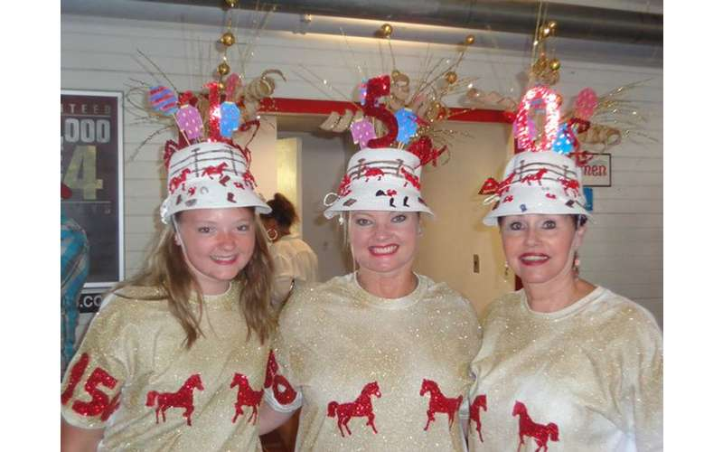 three women with decorated hats