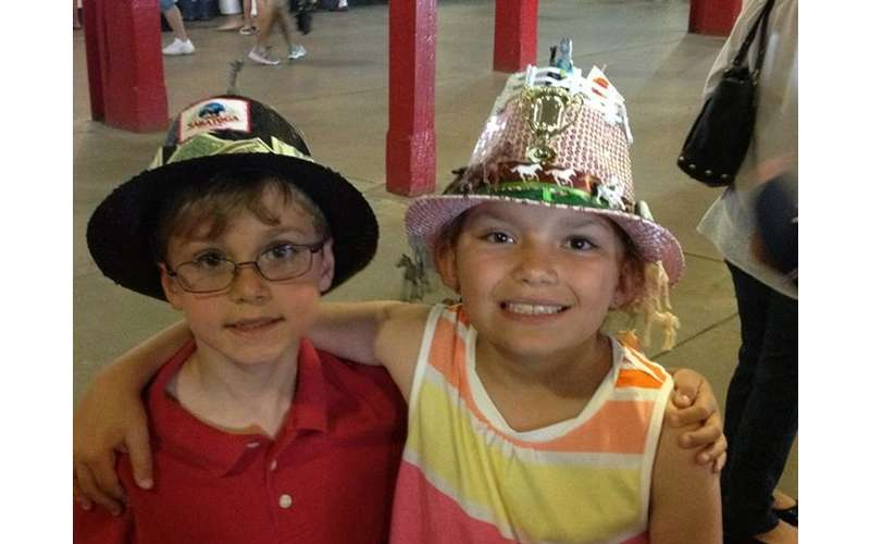 two kids with saratoga race course themed hats