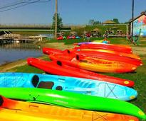 a row of colorful kayaks on the ground