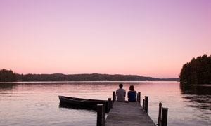two people on a dock overlooking water