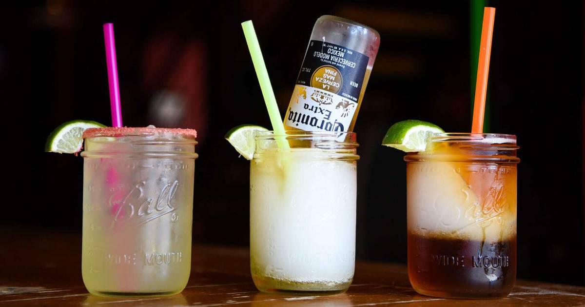 three alcoholic beverages in mason jars