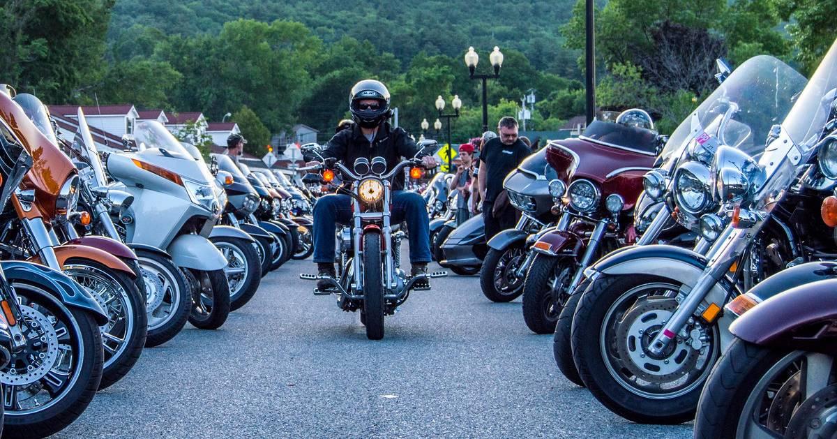 man on motorcycle in between more motorcycles