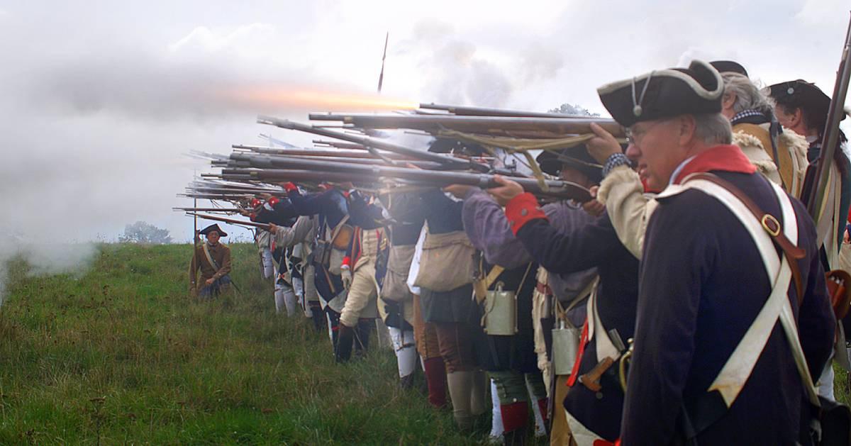 revolutionary war recreationists firing muskets