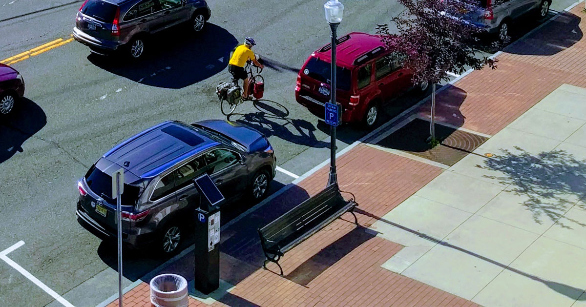 man rides bike next to parked cars