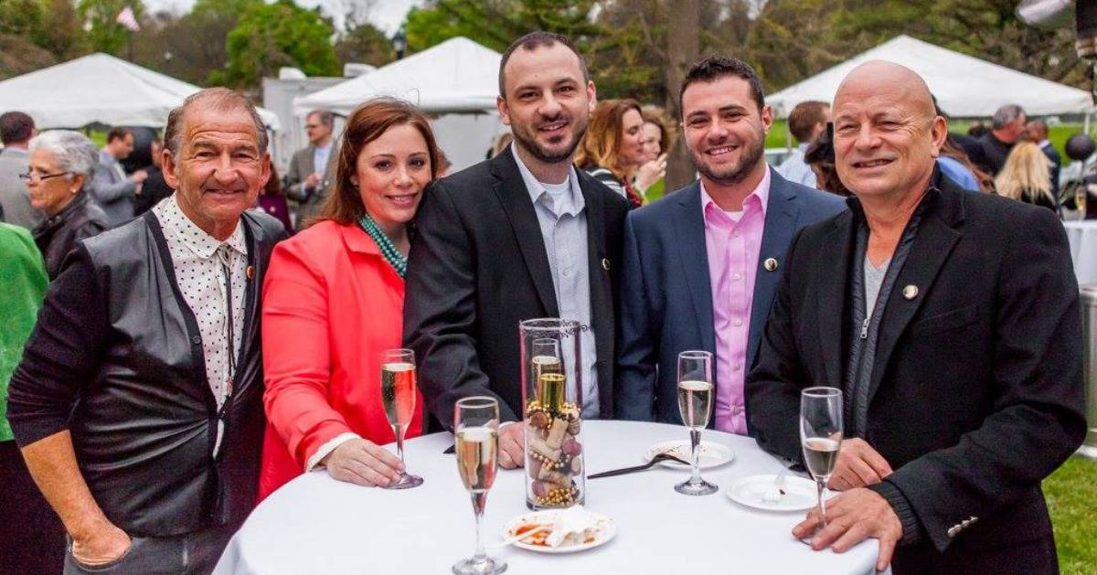 one woman and four men dressed up at outdoor gala