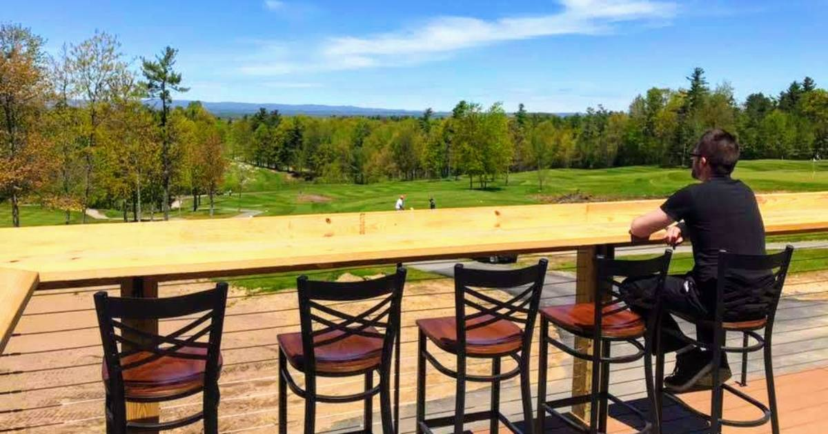 person on stool outdoors looking out at golf course
