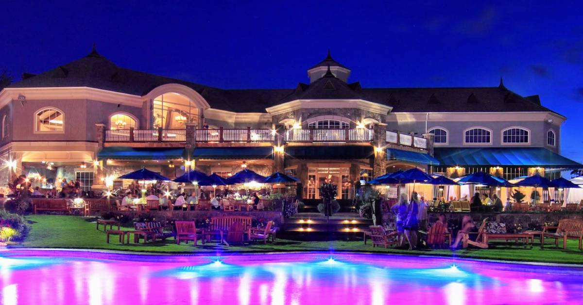 elaborate patio dining at night, purplish lights, there's water