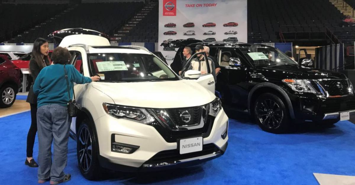 people checking out new cars at an auto show