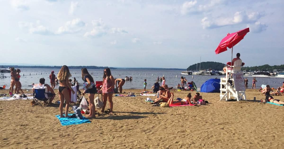 people at a sandy beach at a lake