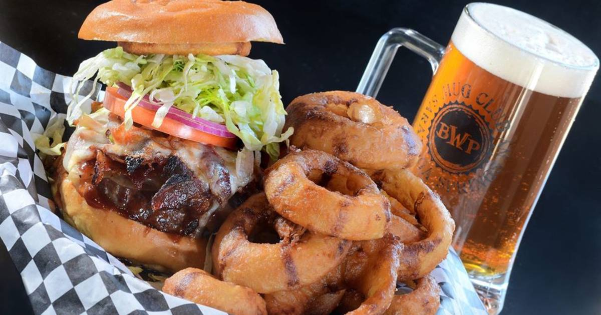 basket with a burger and onion rings, plus a mug of beer