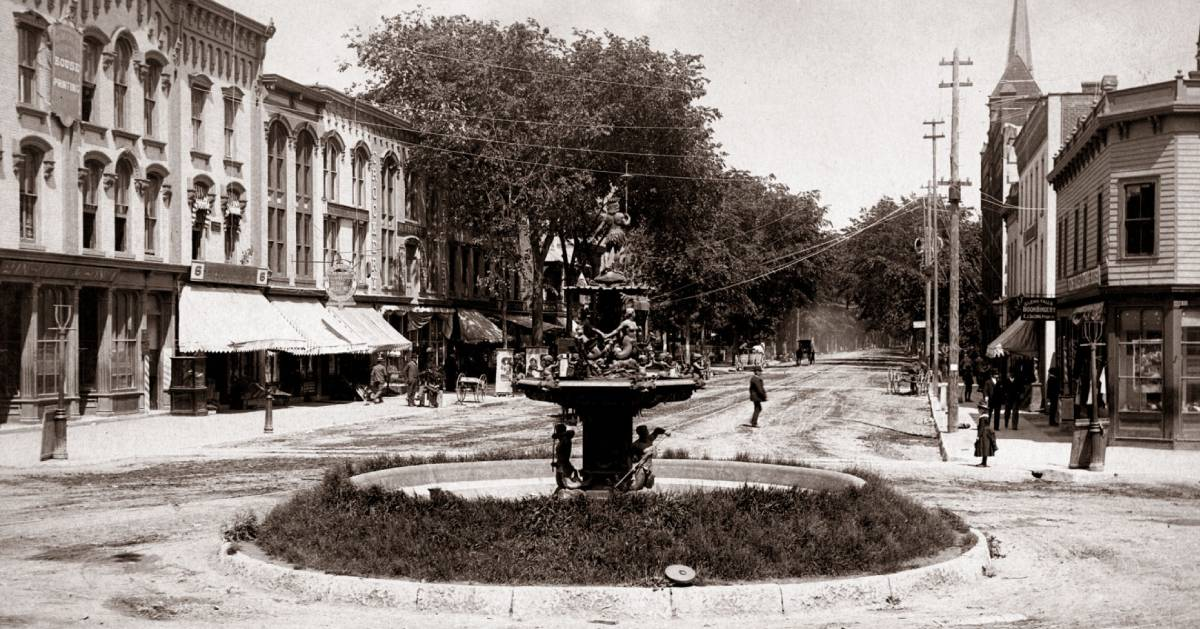 black and white photo of street and fountain in Glens Falls