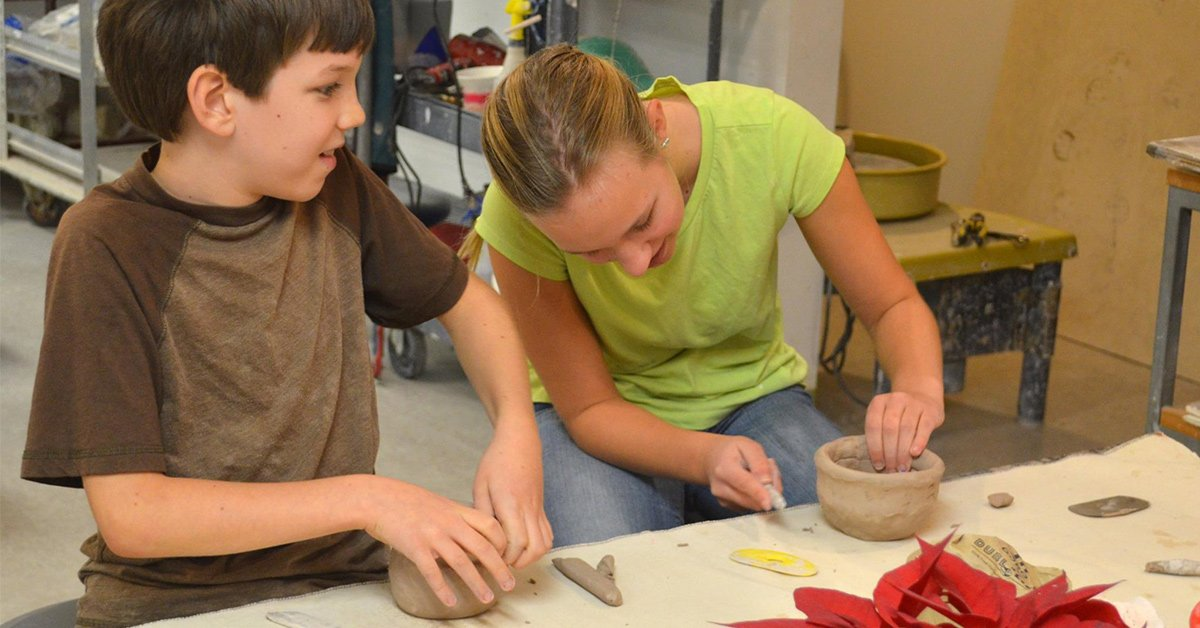 two kids working with clay