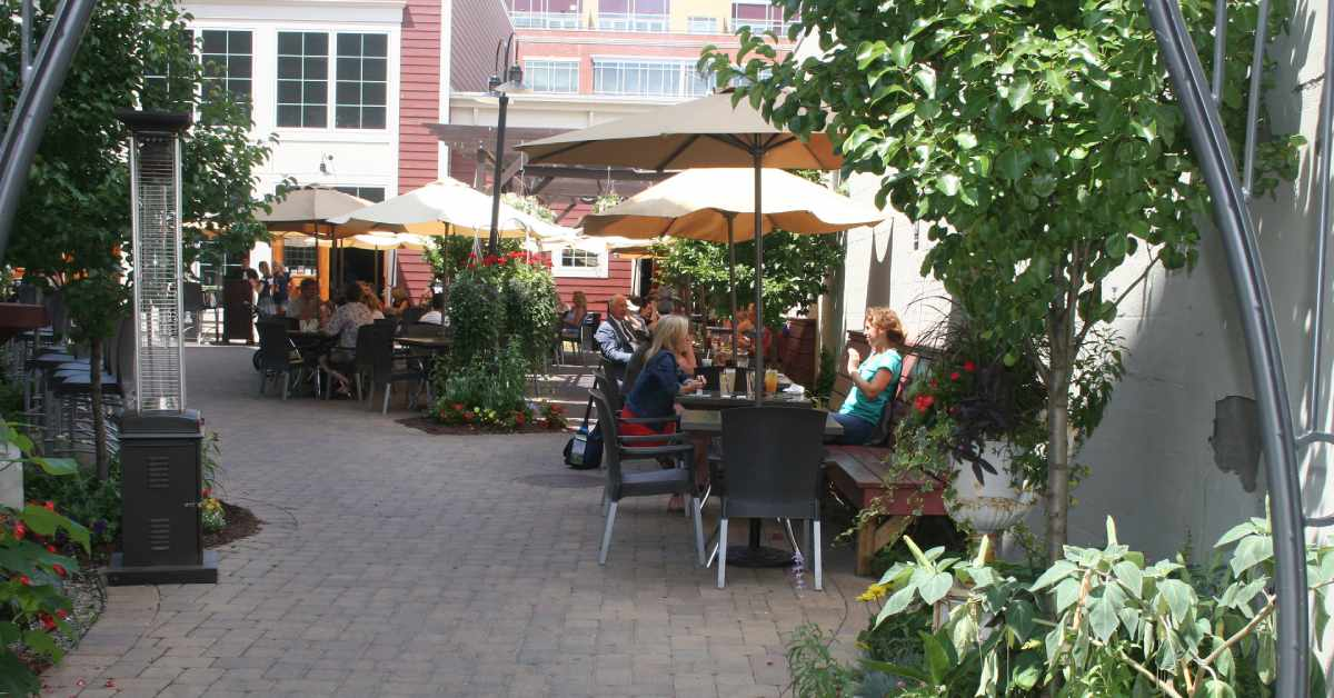people sitting at tables on a patio