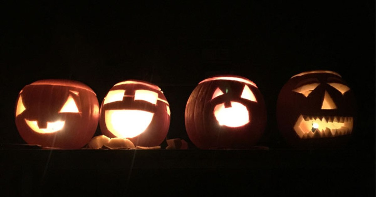 four jack o lanterns in the darkness