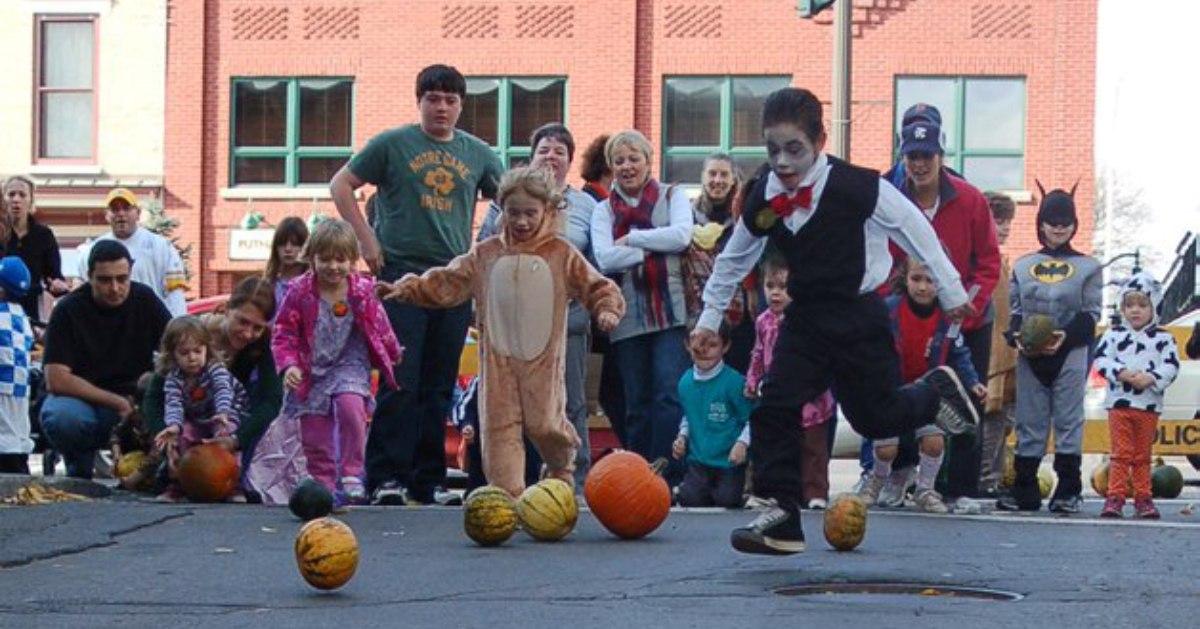 kids doing pumpkin bowling on street