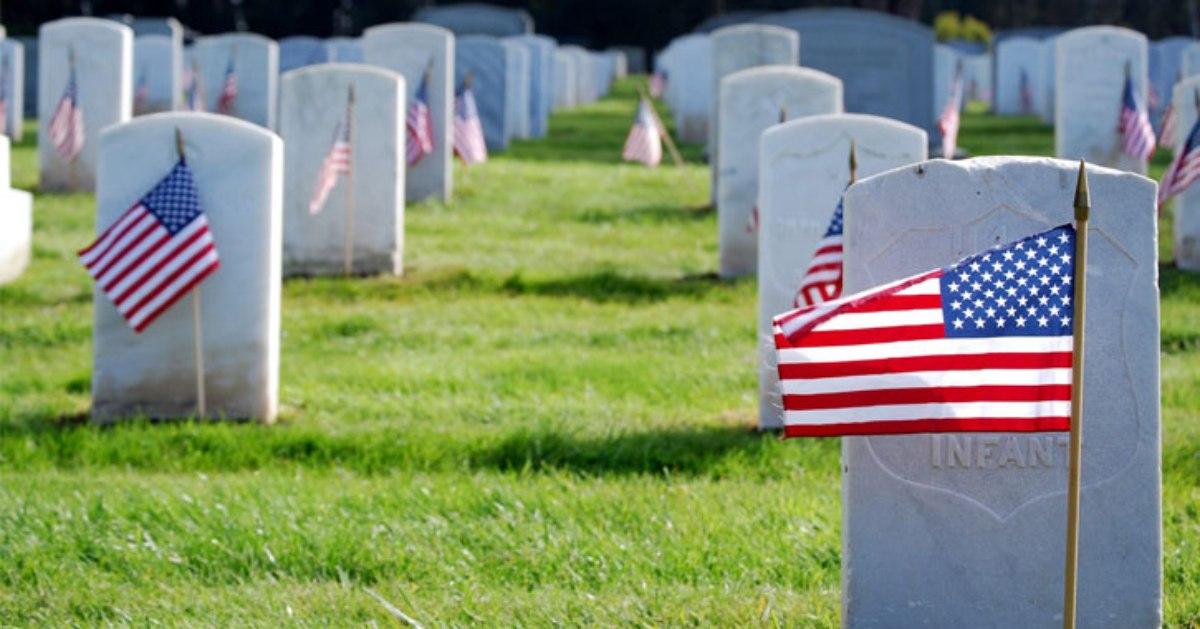 american flags by gravestones