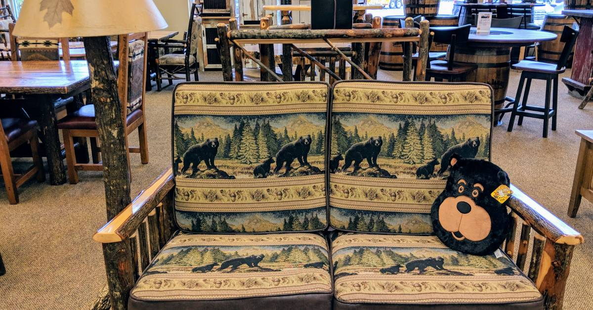 bear-themed loveseat and pillow in furniture store