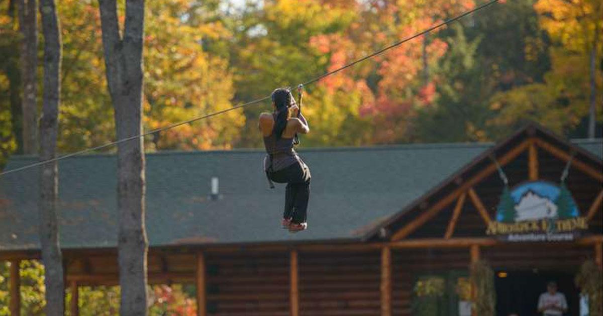 woman ziplining in the fall