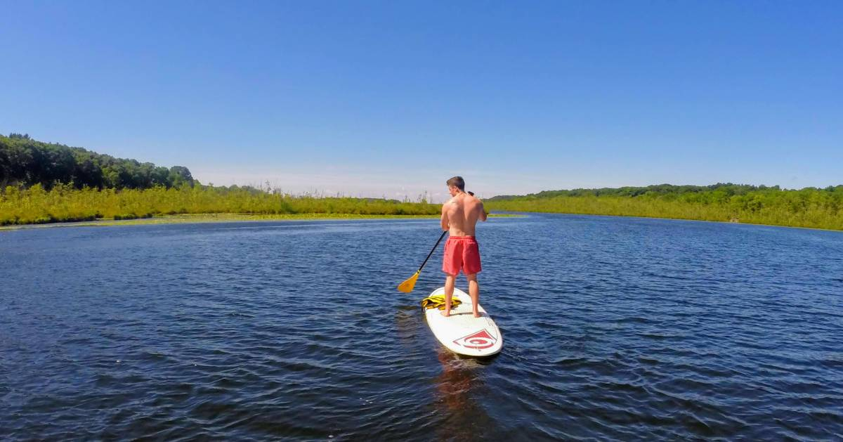 a guy standup paddleboarding