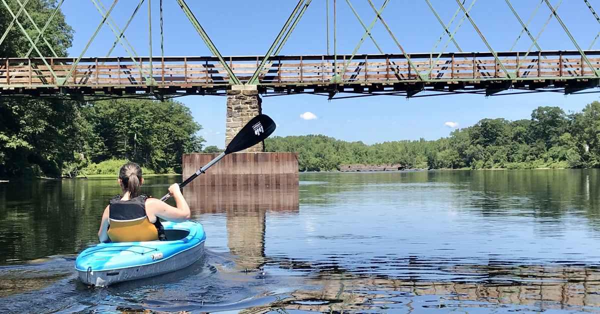 woman paddling in a blue kayak