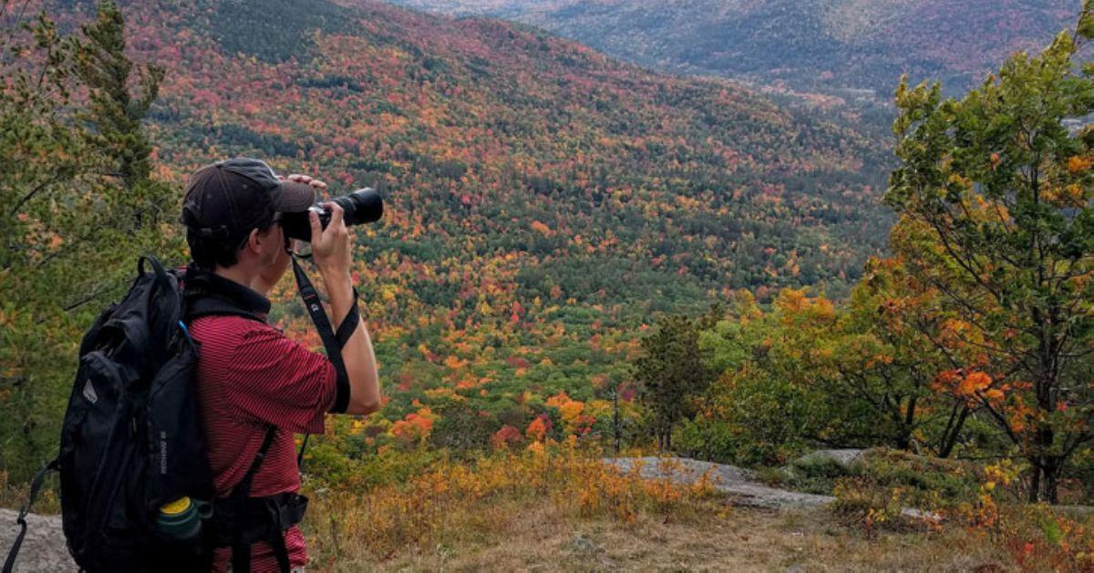 man looking at mountain view through binoculars
