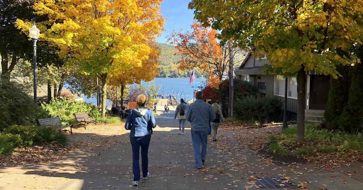 people walking on sidewalk toward lake