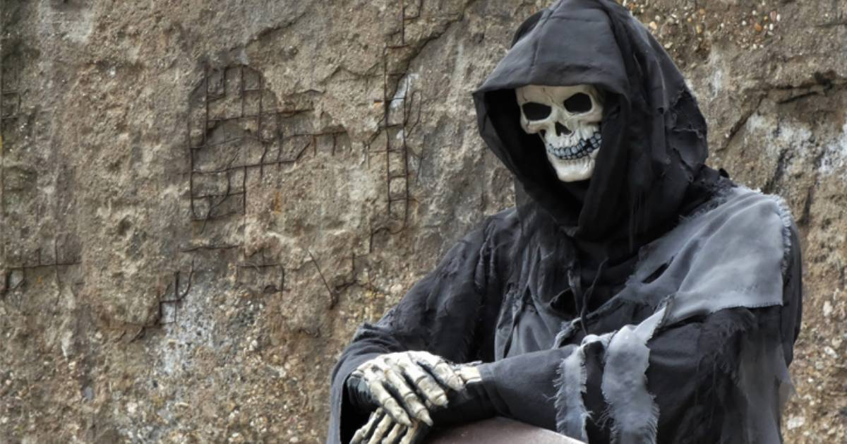 a skeleton in a grim reapers outfit, folding his hands together creepily