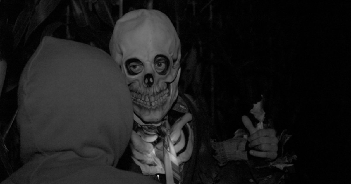 person encountering another person in a skull mask