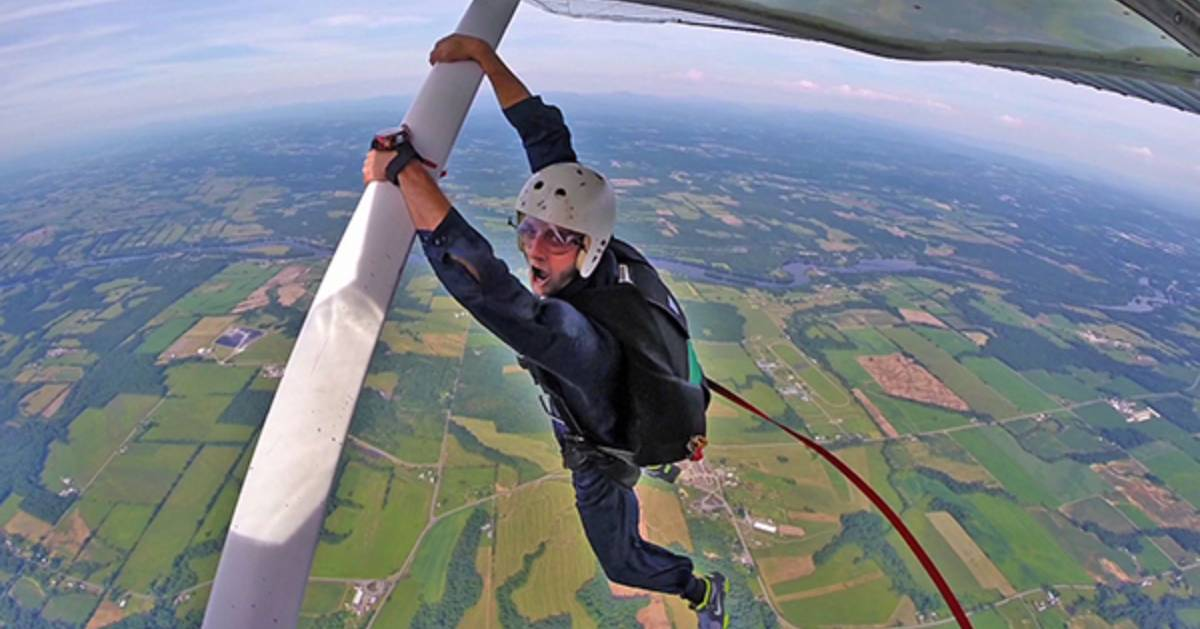 skydiver hanging onto plane
