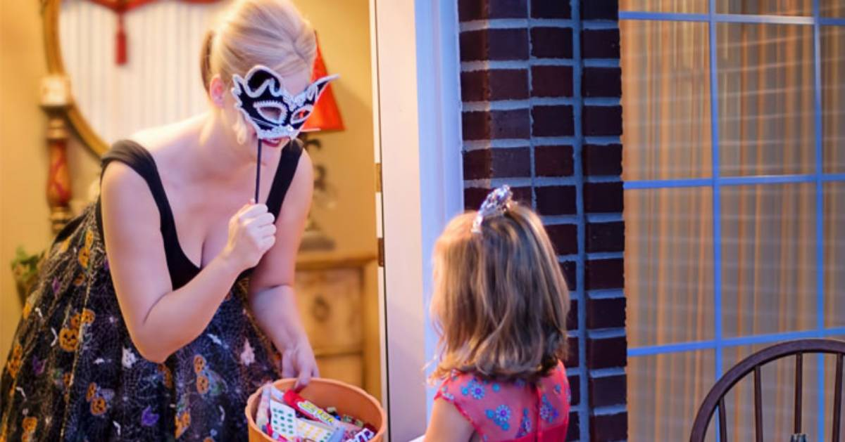 a woman with a masquerade ball mask answering the door for a little girl trick-or-treating