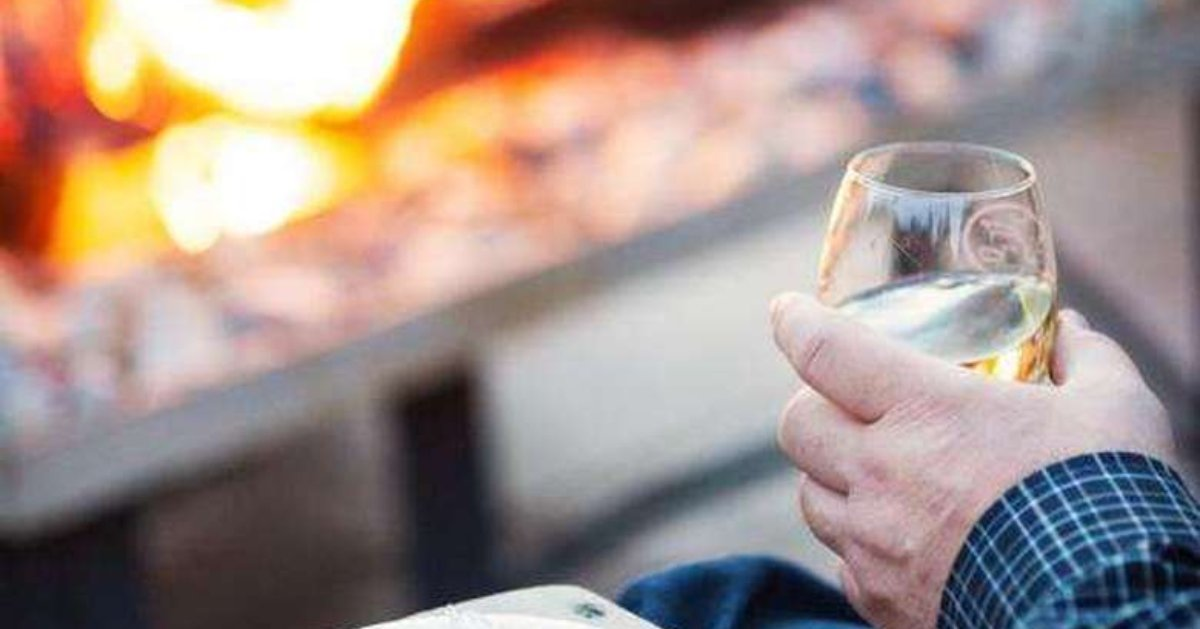 person holding wine glass near firepit on patio