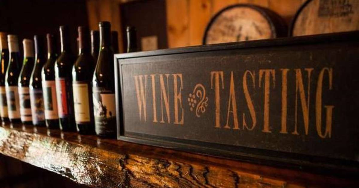 a wine tasting sign next to wine bottles