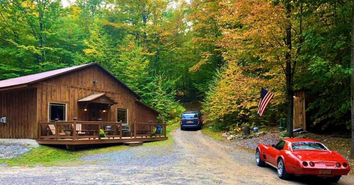 rustic building in the woods with cars nearby