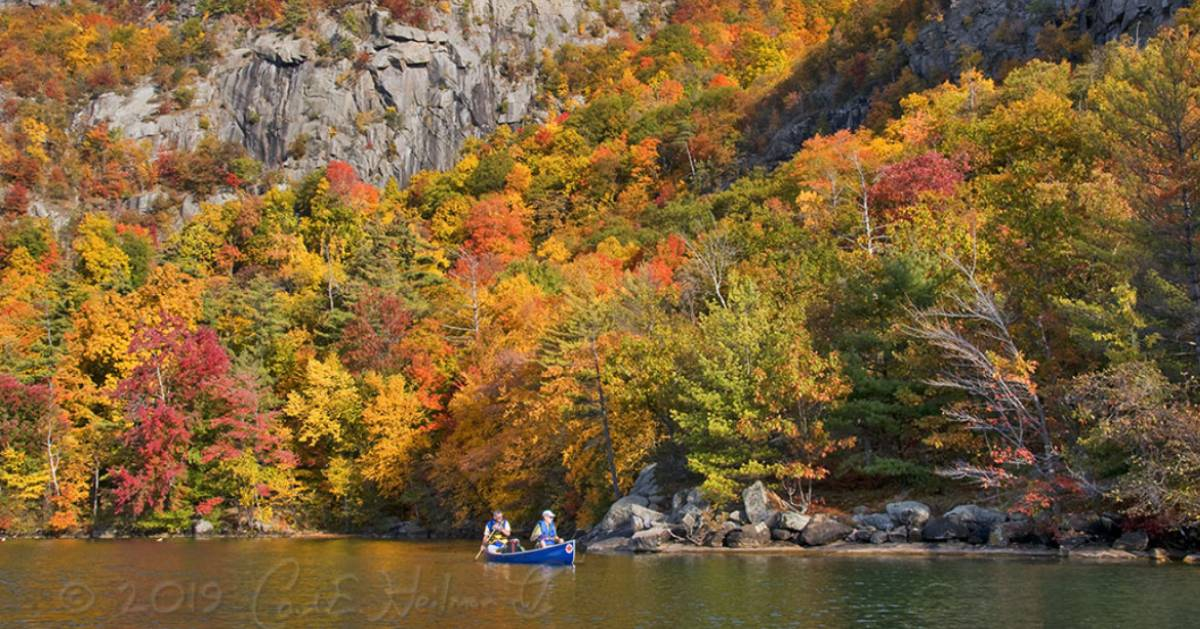 people in a boat on a lake in the fall